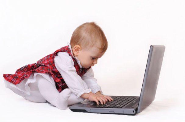 Bebé superdotado escribiendo en ordenador portatil