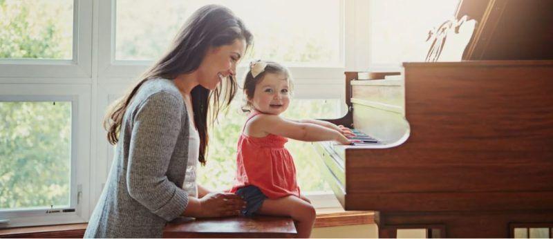 Niña toca piano junto a mamá
