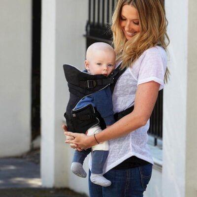 Mama sonríe mirando bebé en su portabebés