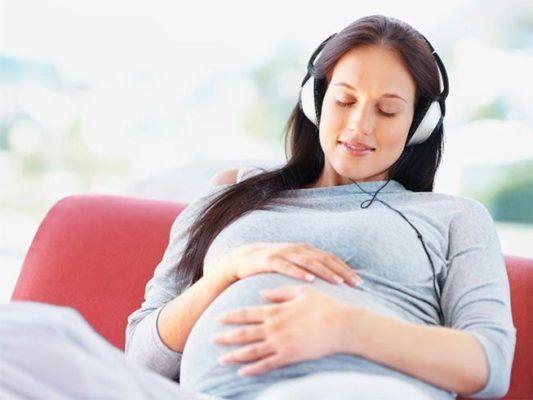 Embarazada escuchando música con auriculares